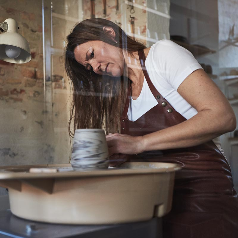 Artisan working on a pottery wheel in her creative studio